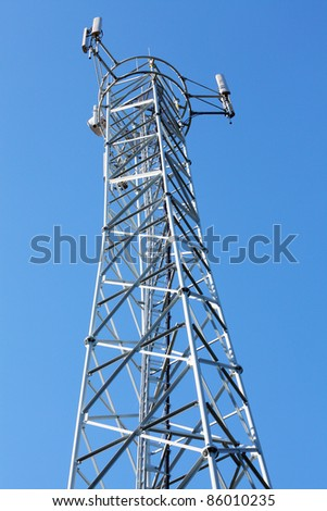 Telecommunications tower with a lot of different antenna against blue sky.