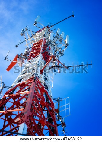 Telecommunications tower with a lot of different antenna under clear sky. - stock photo