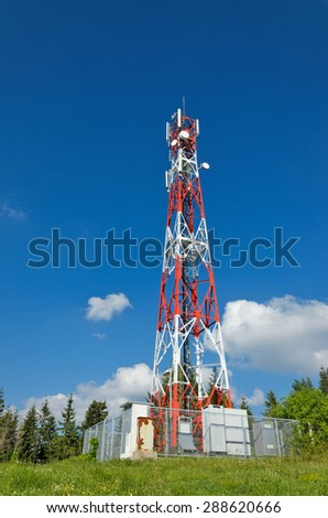 Telecommunications tower with blue sky and clouds - stock photo