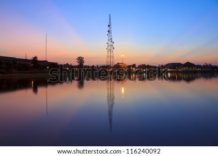 Telecommunications towers near the secret sky after the Sun's reflection in a pond. - stock photo