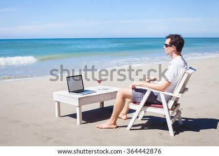 telecommuting, businessman relaxing on the beach with laptop and cocktail, freelancer workplace, dream job