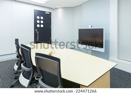 teleconferencing, video conference and telepresence business meeting room with display screen - stock photo