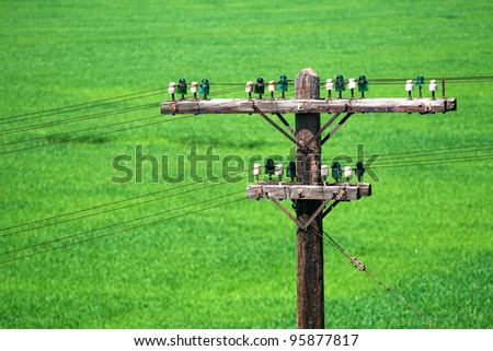 telegraph pole with ceramic supports on green background - stock photo