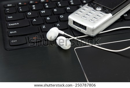 Telemarketing and remote work set: Laptop (notebook), headphones and cell phone on the keyboard. - stock photo