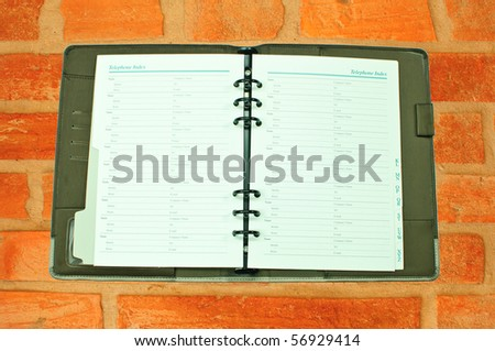 Telephone book on brick wall - stock photo