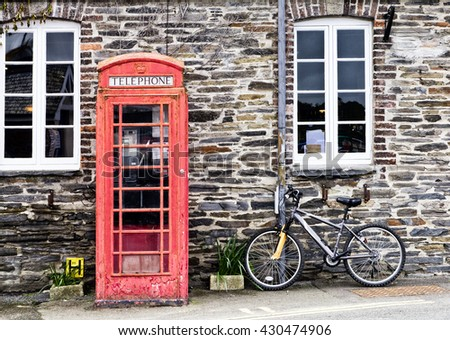 Telephone box and bicycle; Traditional UK red telephone box and bicycle in English village setting  - stock photo