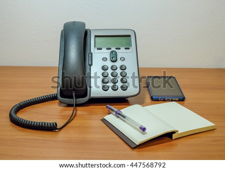 telephone on working table in room service network and internet office with note book