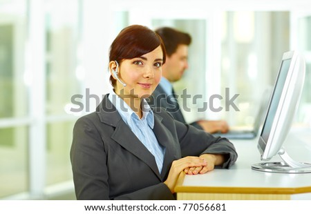 Telephone operators at the monitors smiling at the office - stock photo