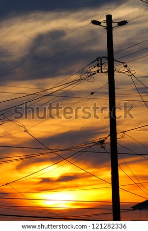 Telephone Pole and Wires against Sunset - stock photo