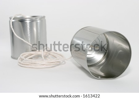 Telephones made out of tin cans and a string, emphasis on one side's tin can, up close - stock photo