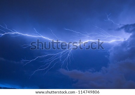 Telephoto of Blue lightning strike during an electrical storm in Florida - stock photo