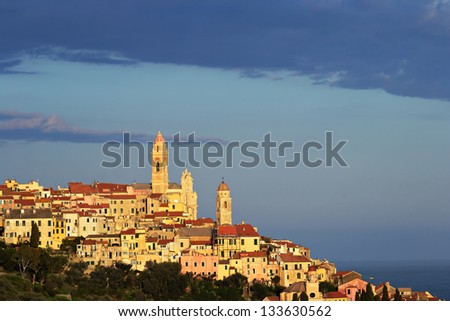 Telephoto view of Cervo old town, Liguria, Italy, with the beautiful baroque church arising from the houses, under evening warm sunlight. - stock photo