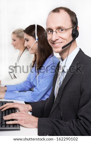 Telesales or helpdesk team - helpful man with headset smiling at camera - stock photo