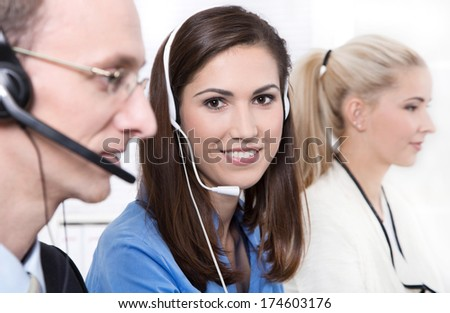 Telesales or helpdesk team - helpful woman with headset smiling at camera - workers at call center - stock photo