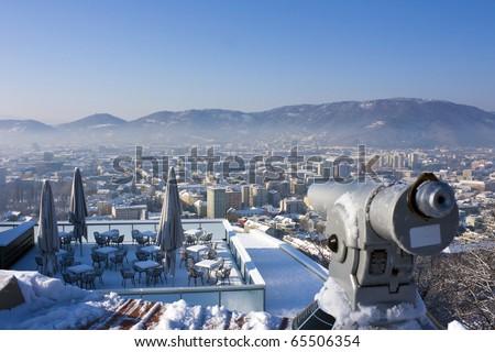 Telescope and terrace of restaurant in winter over snowy Graz, Austria, Europe - stock photo
