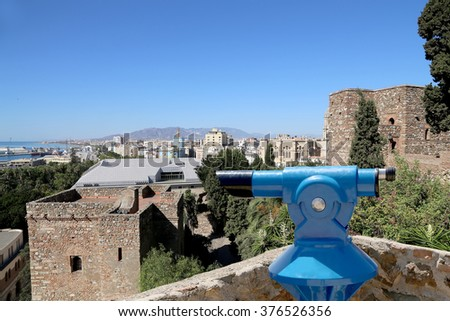 Telescope viewer overlooking the Alcazaba castle on Gibralfaro mountain. Malaga, Andalusia, Spain. The place is declared UNESCO World Heritage Site - stock photo
