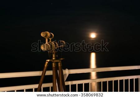 Telescope with amazing moonrising over the sea - stock photo