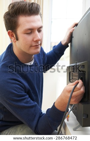 Television Engineer Installing New Television At Home - stock photo