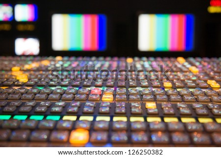 Television gallery with selective focus on the foreground vision mixing panel and TV monitors out of focus in the background. - stock photo