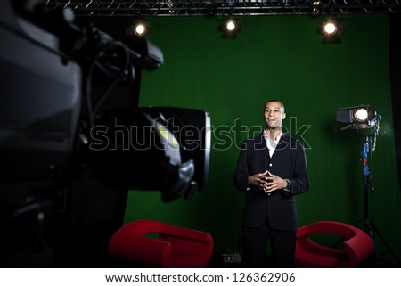 Television presenter in a green screen studio with television camera out of focus in the foreground.