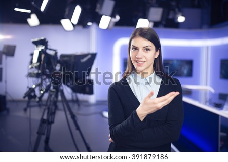 Television presenter recording in news studio.Female journalist anchor presenting business report,recording in television studio,showing hands gesture and talking to the camera..News behind the scenes - stock photo