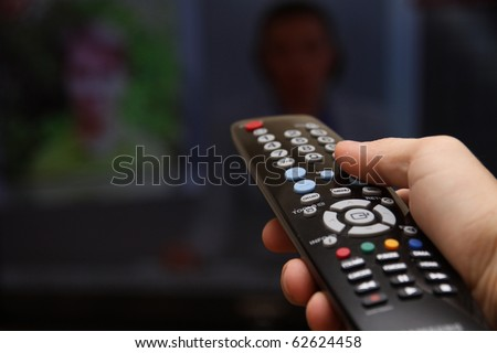 Television remote control changes channels thumb on the blue TV screen - stock photo