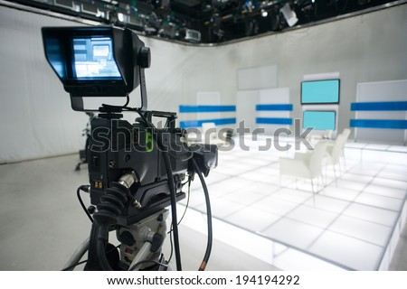 Television studio with jib camera and lights - camera on a crane. Shallow depth of field - focus on camera  - stock photo