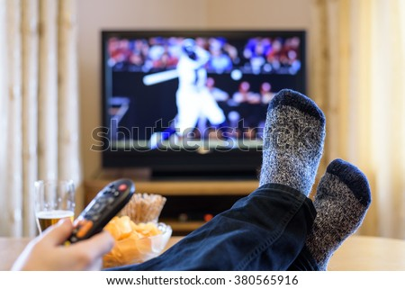 Television, TV watching (baseball match) with feet on table eating snacks and drinking beer - stock photo - stock photo