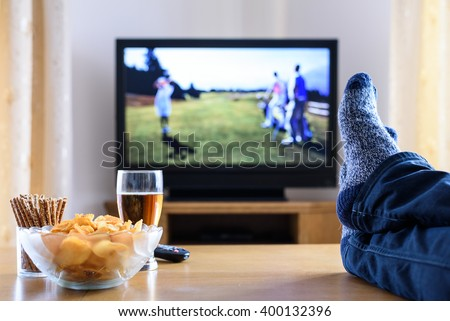 Television, TV watching (golf game) in living room with feet on table - stock photo - stock photo