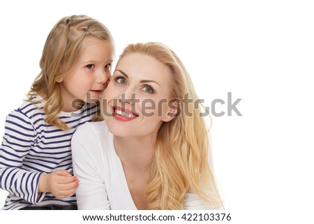 Tell her everything. Portrait of a little cute girl whispering to her mother at the studio on white background. - stock photo