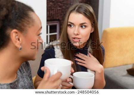 Telling the hottest gossip. Cropped image of two beautiful young women gossiping while sitting in the restaurant - stock photo