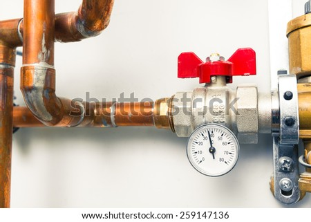 temperature gauge indicator with water tap in boiler-room - stock photo