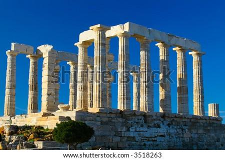 temple of poseidon on the cliff side overlooking the aegean sea - stock photo