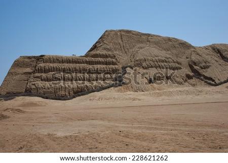 Temple of the Sun (Huaca del Sol). Large historic adobe temple from the Moche culture located close to Trujillo in Peru. - stock photo
