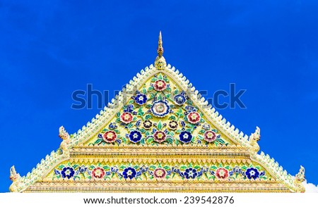 temple rooftop decorate with naga and porcelain flower