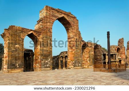 Temple ruins and the Iron Pillar in the Qutb complex, Delhi, India  - stock photo