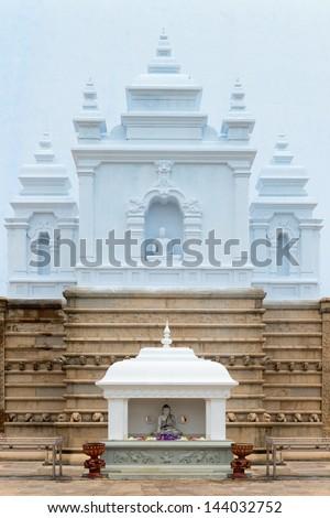 Temple with Buddha image statues near white sacred stupa Ruwanmalisaya dagoba, Anuradhapura, Sri Lanka - stock photo