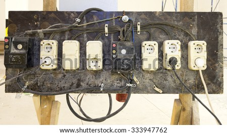 Temporary panel with plugs and switches, on the building site - stock photo
