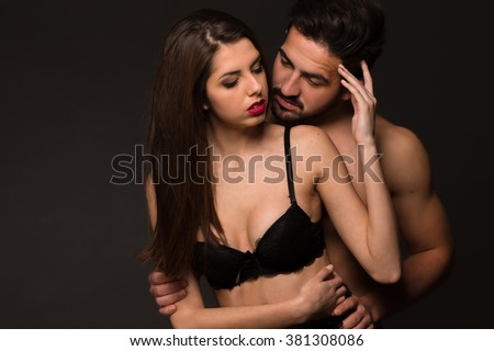 Temptation between woman and man in studio. Petty lady with long dark hair touching her boy-friend's hair.