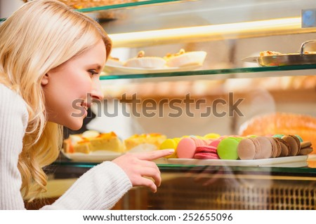 Tempted by a fantastic confection. Attractive young blonde woman buying some macaroons in a confectionery shop while standing in front of a windowsill with various desserts - stock photo