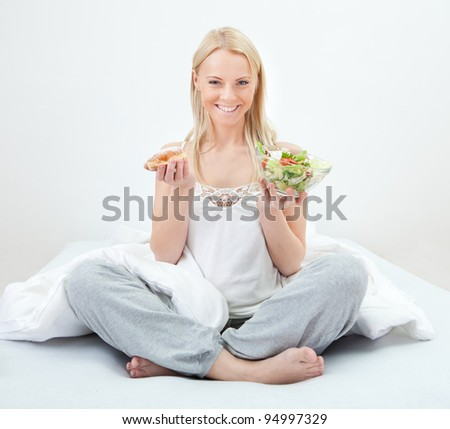 Tempted young woman making a food choice - stock photo