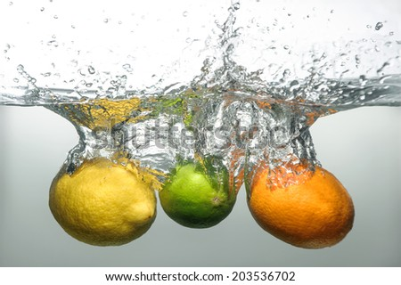 Tempting ripe orange, lemon and lime falling down into the water with big splash and bubbles