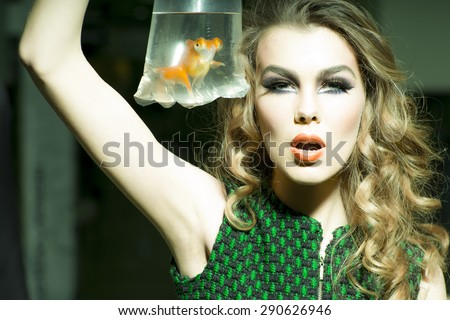 Tempting young girl with bright makeup and blonde curly hair holding cellophane package aquarium with goldfish, horizontal photo - stock photo