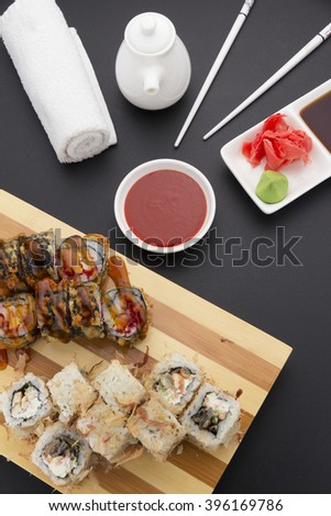 Tempura and shavings of tuna sushi roll on wooden plate ( gete ) with ginger wasabi chopsticks and sauces over black background - stock photo