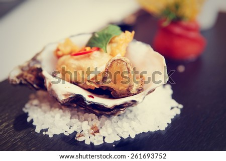 Tempura fried oyster in shell, delicious appetizer, toned image - stock photo