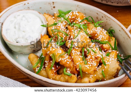 Tempura -  fried squid rings served green onion on wooden table with sauce - stock photo
