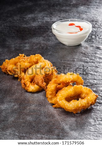 Tempura squids with pepper and mayo sauce on stone texture - stock photo