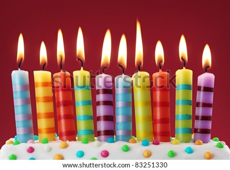Ten colorful candles on red background