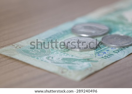 Ten Dirham Note and Coins, Currency of the United Arab Emirates on wooden table - stock photo