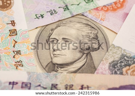 Ten dollar bill surrounded by Chinese Yuan - stock photo